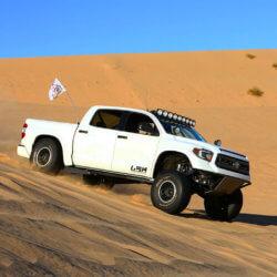 Badass Toyota Tundra prerunner jumping in the dunes