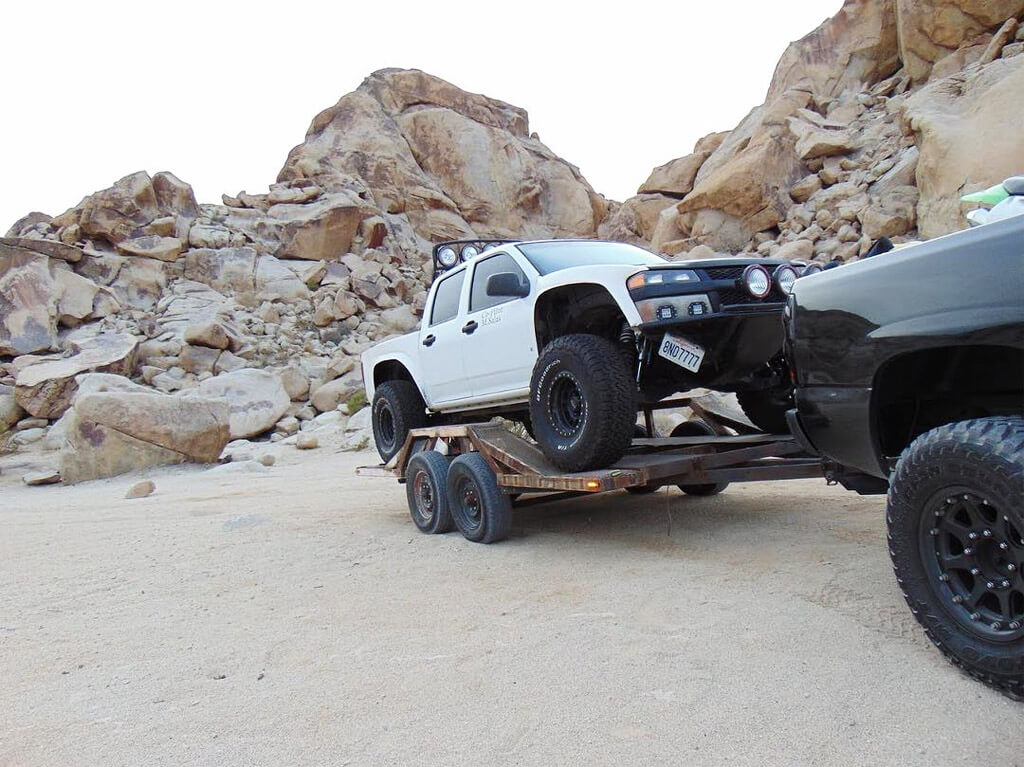Prerunner truck towed on a trailer