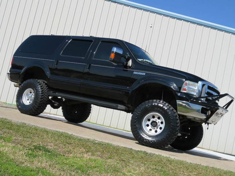 Big Black lifted SUV - Ford Excursion with large wheels and steel Bumper
