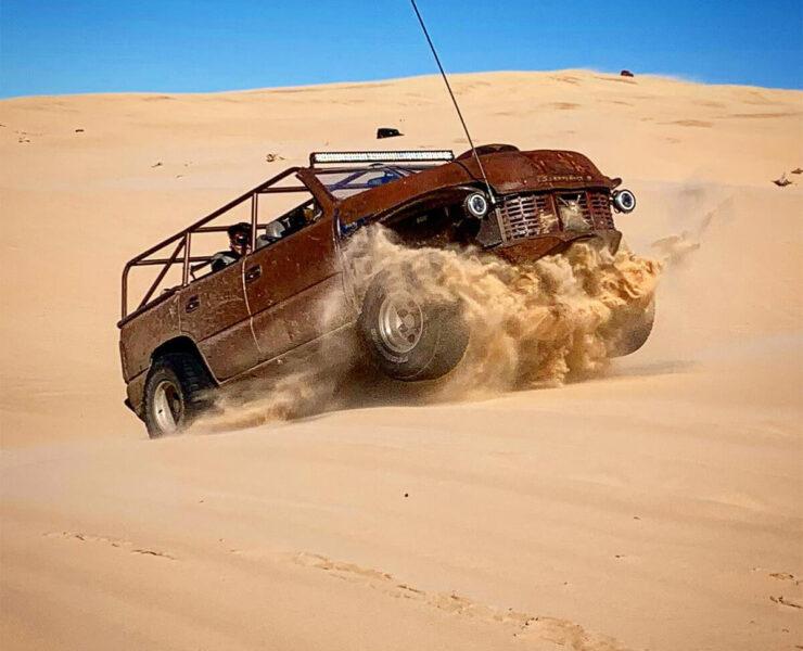Jumbing dunes in a rat rod buggy