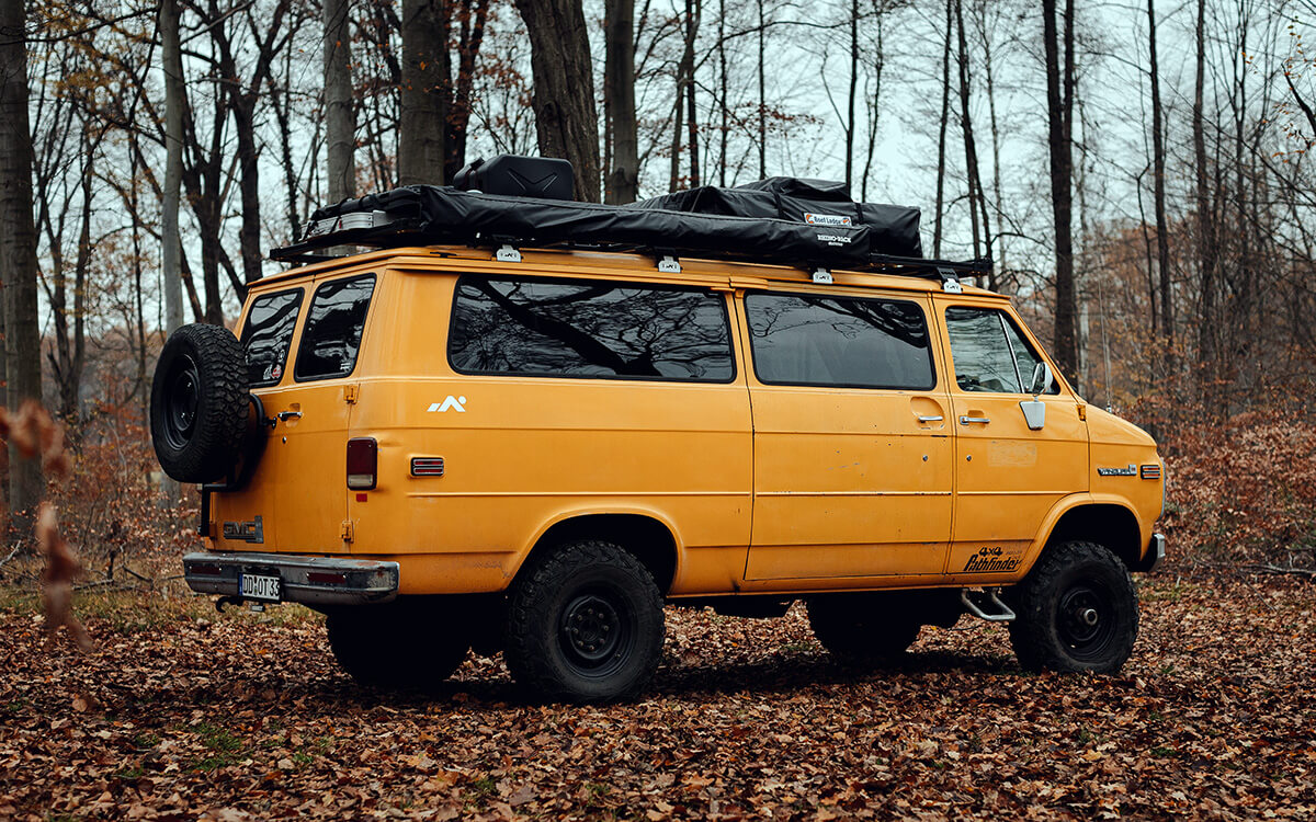 GMC camper van with a spare tire and a roof rack 235/85R16 Kumho MT 71