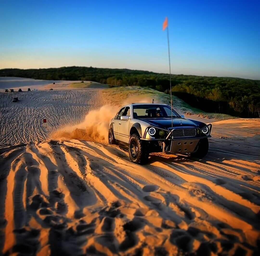 Mercedes E-Class sand offroading through the dunes of a desert