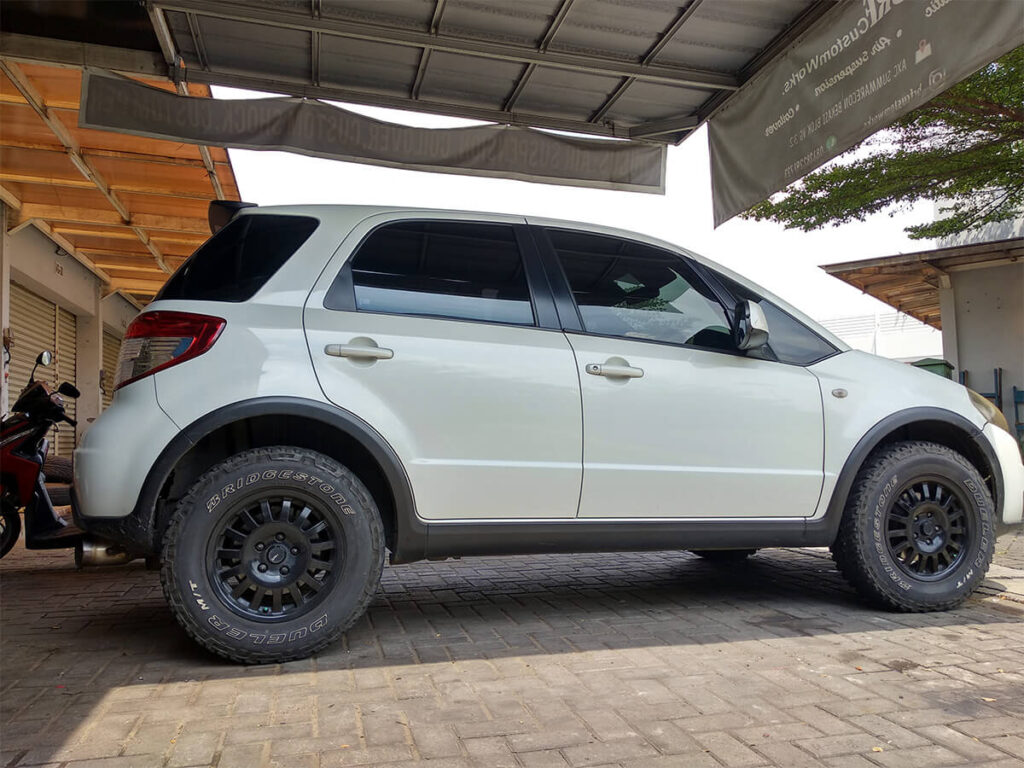 White Lifted Suzuki SX4 with off-road wheels and a lift kit