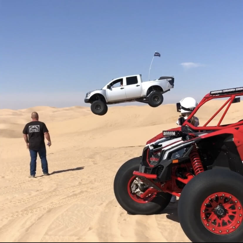 Long travel Nissan Titan Prerunner sending it jumping the dunes